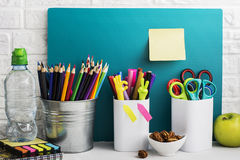 School background: a white brick wall with accessories, pencils, tetrads, scissors, an apple, pecans, a board for a Stock Photos