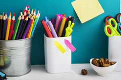 School background: a white brick wall with accessories, pencils, tetrads, scissors, an apple, pecans, a board for a Stock Images