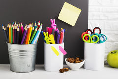 School background: a white brick wall with accessories, pencils, tetrads, scissors, an apple, pecans, a board for a Royalty Free Stock Photos