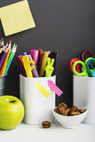 School background: a white brick wall with accessories, pencils, tetrads, scissors, an apple, pecans, a board for a Stock Photo