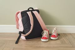 School backpack and sneakers on the floor in home interior. School backpack and sneakers on the floor in a home interior Stock Images