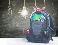 School backpack with supplies. School backpack full of supplies on white desktop, blackboard with drawn idea lamps in background Stock Photography