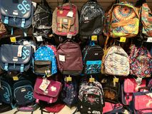 School backpacks for kids. Hanging in the supermarket royalty free stock photo
