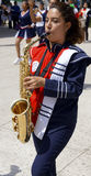 School band march girl playing saxophone. Mexican girl plays the saxophone in a school band march competition in mexico, teenager girl musician in a exhibition Royalty Free Stock Photography