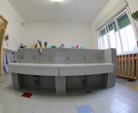School bathroom with large ceramic sink without children stock photography