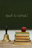 School bell and books on desk with chalkboard. In background Royalty Free Stock Images