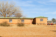 School Bell`s Ringing!. PITSENG, LESOTHO - AUGUST 10, 2016: Schoolchildren line up in front of a rural primary school on a winter`s morning; free, compulsory royalty free stock images