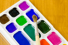 School belonging. Moist colours on a wooden surface Royalty Free Stock Image
