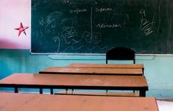 School benches facing blackboard Stock Photography