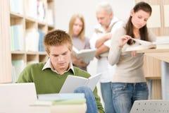 School-Bibliothek - Kursteilnehmer mit Buch Stockbild