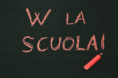School blackboard. Blackboard with the notice W LA SCUOLA and a red chalk Royalty Free Stock Image