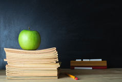 School Blackboard and Teacher's Desk. A school teacher's desk with stack of exercise books and apple in left frame. A blank blackboard in soft focus background Royalty Free Stock Photo