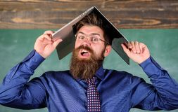 School blows his mind. Hipster teacher aggressive with laptop as roof goes mad about teaching. Can not get used to. Teachers lifestyle. Teacher bearded man with royalty free stock image