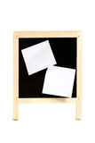 School board with adhered bits of paper. Two white clean peel-off labels glued to child blackboard isolated on white background Stock Photo