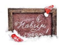A school board with a festive inscription, a New. Happy New Year. A school board with a festive inscription, a New Year`s cap and a boot in the snow Stock Photo