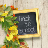 School board with the inscription `First September`. And a bouquet of autumn leaves on wooden background. School background Royalty Free Stock Photography