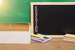 School book on desk, education concept. School text book with chalk,eraser and blackground on desk, education concept Royalty Free Stock Image
