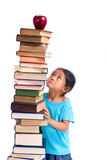 School books. A young asian girl looking up at an apple ontop of a big pile of books Stock Photography