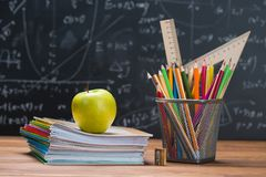 School Books And Stationery On A Wood And A Chalkboard Background Royalty Free Stock Image