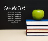 School books with apple on desk Royalty Free Stock Photos