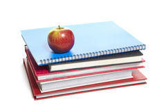 School books and apple on white background Stock Image