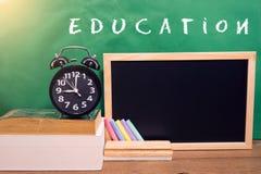 School books and clock on desk, education concept. School books with blackboard and clock on desk, education concept Stock Photos