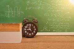 School books and clock on desk with green board, education. Concept Stock Images