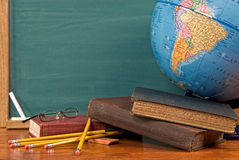 School books on a desk. Old school books on a desk with a globe in front of a green chalkboard Stock Image