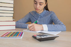 School books on desk, education concept. Girl doing lessons at home. School books and pencils on desk, education concept. Girl doing lessons at home Royalty Free Stock Photo