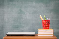School books on desk, school supplies. Books and blackboard background, Online education, education concept royalty free stock image