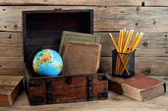School books with globe and pencils in the old chest Stock Photo