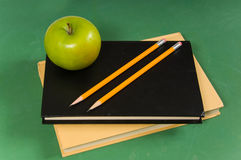School books with green apple Royalty Free Stock Photos