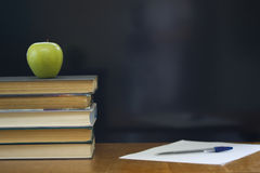 School books with green apple on desk. Royalty Free Stock Photos