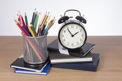School books, pencil crayons and an alarm clock. Set to just before two signalling the end of the lunch break and return to classes or home time Royalty Free Stock Images