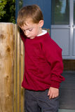 School boy. In uniform by fence Stock Images