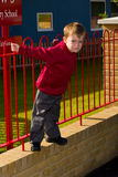 School boy. In uniform by fence Stock Photo