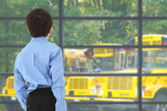 School Boy. Looking out window at busses in parking lot Royalty Free Stock Images