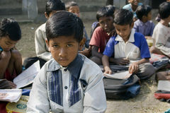 A School boy. A child boy is reading book outside the school in rural India Royalty Free Stock Images