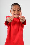 School boy 9 big toothy smile and thumbs up sign. Young school boy, 9, with big toothy smile to camera and both hands giving thumbs up sign stock photo