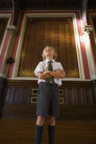 School boy (5-7) with arms crossed in hall by wall plaque, low angle view Royalty Free Stock Photography