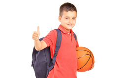 School boy with backpack holding a basketball and giving a thumb Royalty Free Stock Photography