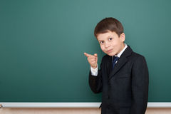 School boy in black suit show finger gesture, on green chalkboard background, education concept Royalty Free Stock Photography