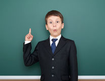 School boy in black suit show finger up gesture and wonder, point on green chalkboard background, education concept Stock Photography