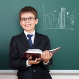 School boy with book, bar chart drawing on chalkboard background, dressed in classic black suit, education concept Stock Images