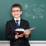 School boy with book portrait, pie chart with percent draw on chalkboard, dressed in classic black suit, education concept Stock Photo