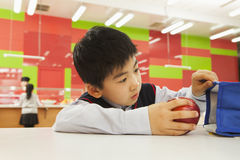 School boy checking lunch bag in school cafeteria Stock Photo