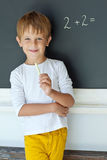 School boy. A child writes on the blackboard Royalty Free Stock Images