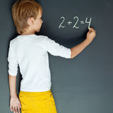 School boy. A child writes on the blackboard Royalty Free Stock Image