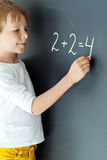 School boy. A child writes on the blackboard Stock Photos