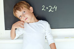 School boy. A child writes on the blackboard Stock Image